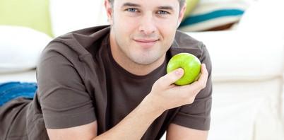 Positive man holding a green apple lying on the floor